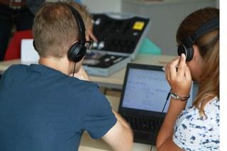 Besucher der Nano Summer School mit Kopfhörern auf einen Bildschirm blickend